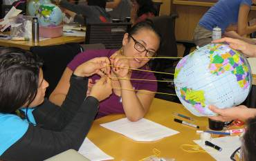 Teachers use string to model sunlight hitting Earth's surface