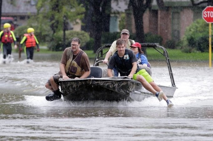 people use boat to navigate flooded streets