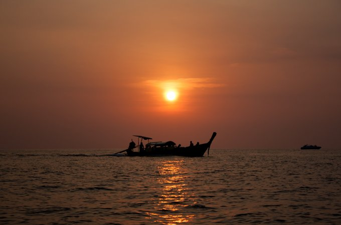 Fishing boat out on the ocean during sunset
