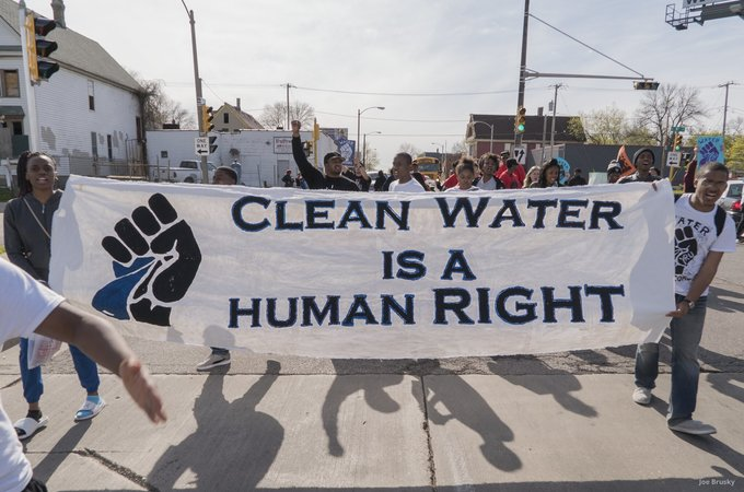 Protestors holding sign that reads clean water is a human right
