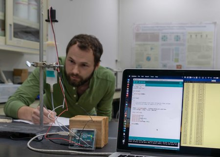 Graduate student, Alex Kendrick, calibrates a sensor in the lab measuring a water level.