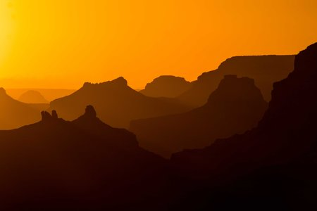 The Grand Canyon, seen from the Desert View Watchtower, falls into silhouette at sunset.