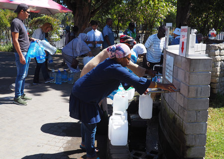 Cape Town citizens filling water bottles at spring