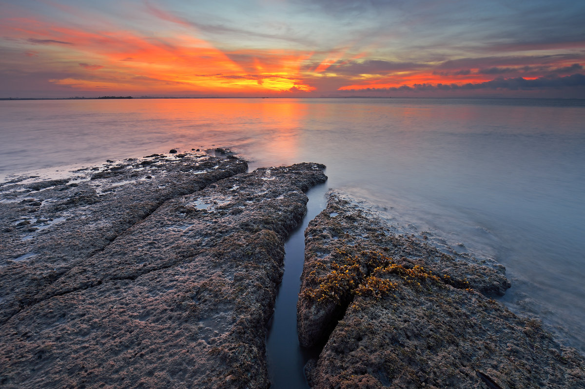 Rock at water's edge at sunset