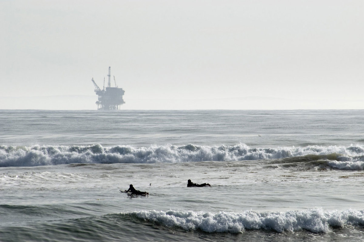 surfers with oil rig in background