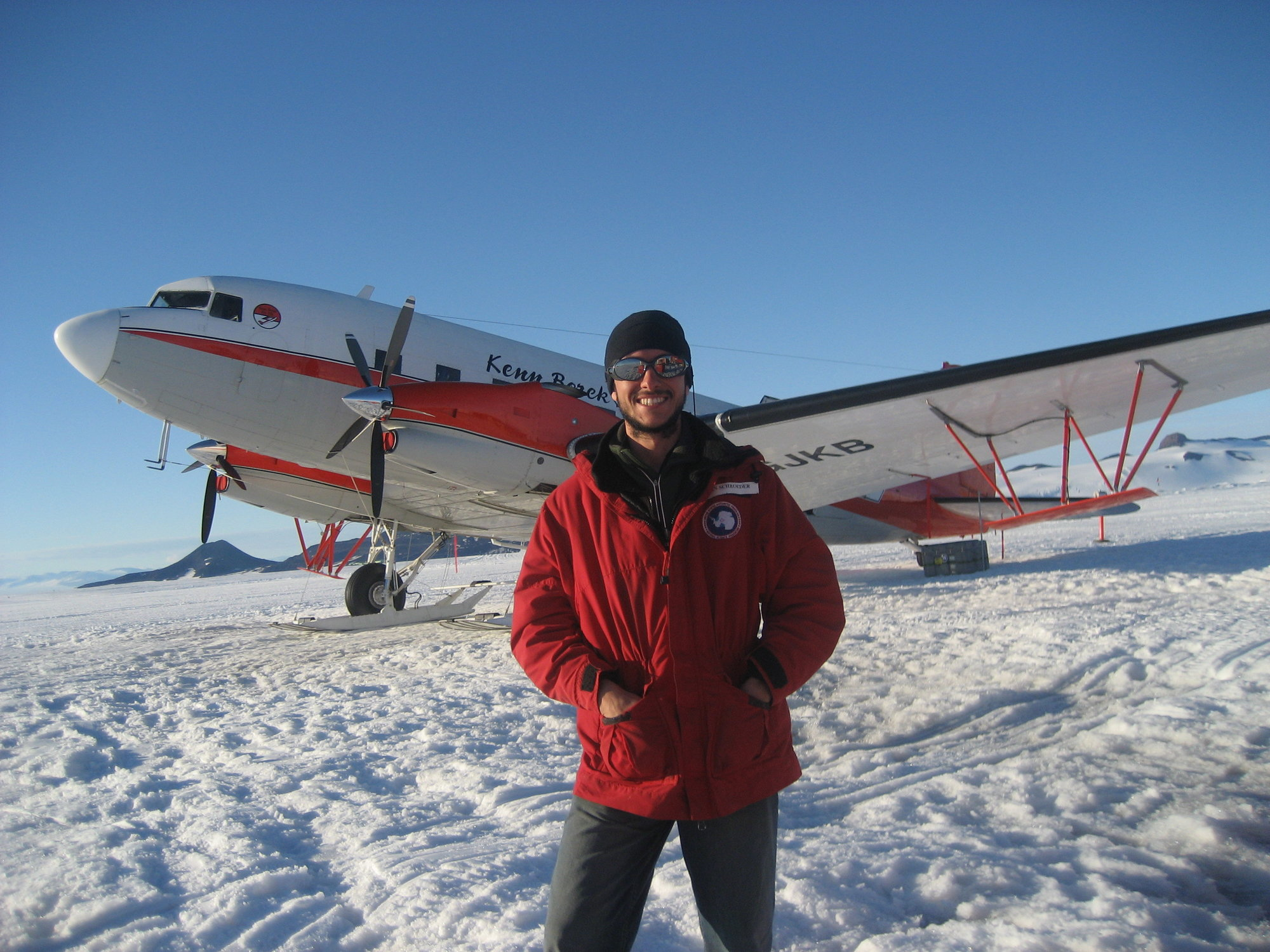 Scientist in front of airplane in Antarctica.