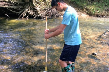 Ethan Jean collecting samples in shallow water