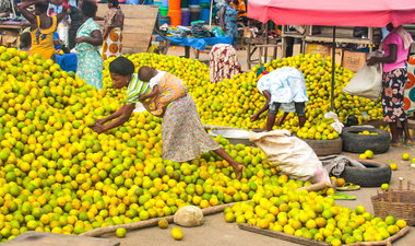 African woman chooses fruit at market.