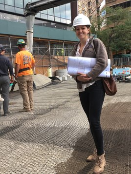Kate Hayes in hard hat holding blueprint